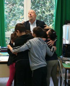 Gino Fanelli presidente di Helpis onlus abbracciato dai bambini della scuola elementare di Lomello